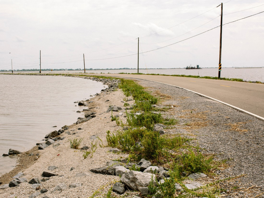 When tides are high and winds are blowing, Island Road sometimes becomes impassable. Isle de Jean Charles is vulnerable to hurricanes and flooding. The marsh is disappearing and seas are rising because of global warming.