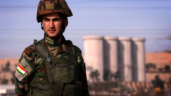 An Iraqi Kurdish Peshmerga soldier stands guard near the Mosul Dam on the Tigris River.