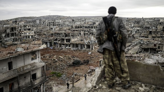 A Kurdish marksman stands atop a building as he looks at the destroyed Syrian town of Kobani on January 30, 2015. After four months of fighting, Peshmerga forces liberated the city from the grip of ISIS.