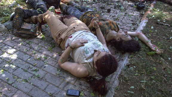 """Two women hold hands after an explosion in Suruc, Turkey, on July 20, 2015. The blast <a href=""""http://www.cnn.com/2015/07/22/world/turkey-suruc-explosion/index.html"""" target=""""_blank"""">occurred at the Amara Cultural Park,</a> where a group was calling for help to rebuild the Syrian city of Kobani, CNN Turk reported. At least 32 people were killed and at least 100 were wounded in the bombing. Turkish authorities said they believed ISIS was involved in the explosion."""