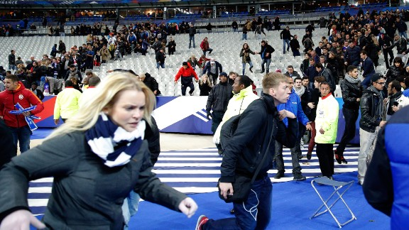 Spectators at the Stade de France in Paris run onto the soccer field after explosions were heard outside the stadium on November 13, 2015. Three teams of gun-wielding ISIS militants hit six locations around the city, killing at least 129 people and wounding hundreds.
