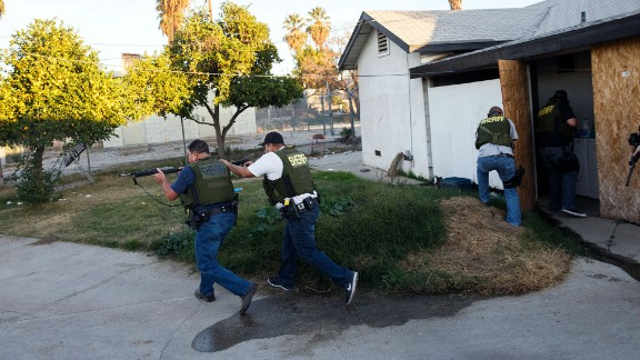 Law enforcement officers search a residential area in San Bernardino, California, after a mass shooting killed at least 14 people and injured 21 on December 2, 2015. The shooters -- Syed Rizwan Farook and his wife, Tashfeen Malik -- were fatally shot in a gunbattle with police hours after the initial incident. The couple supported ISIS and had been planning the attack for some time, investigators said.