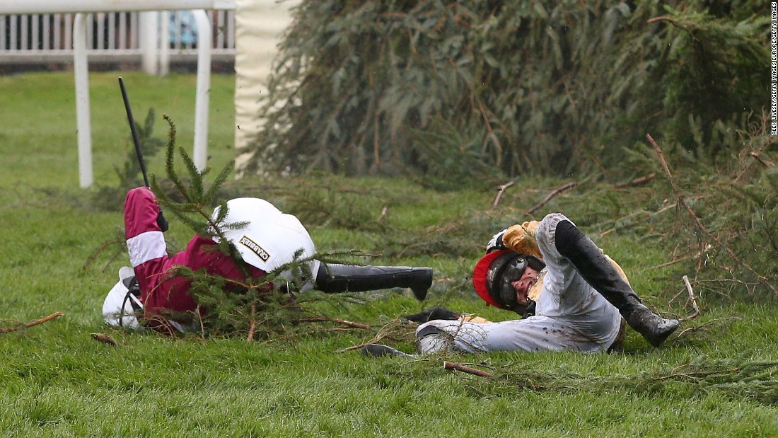 Jockeys Nina Carberry and  P.W Mullins lie on the ground after falling from their mounts at The Chair fence -- an occupational hazard in the race business.