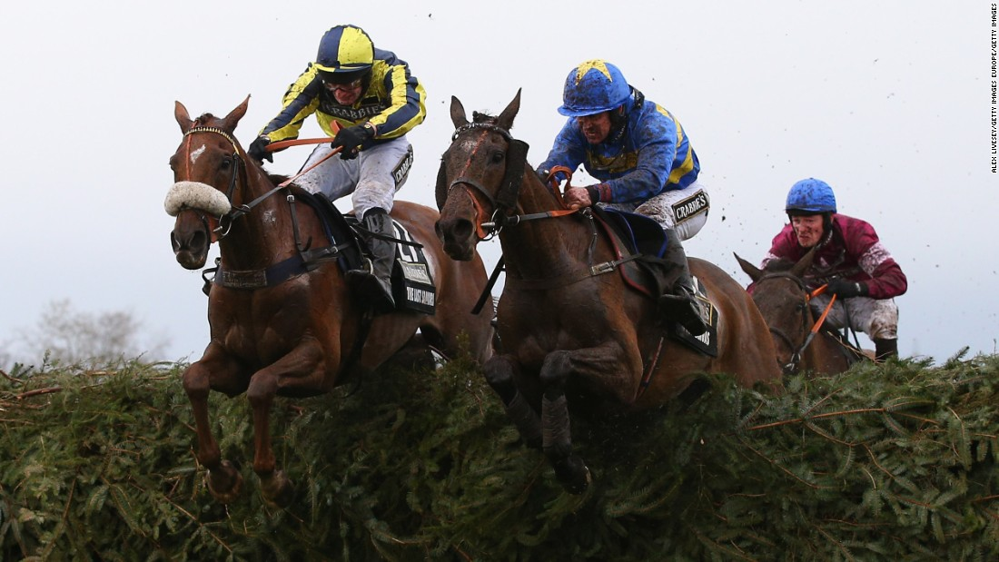 The Last Samuri (R) ridden by David Bass and Vics Canvas (L) ridden by Robert Dunne clear the last fence. However, in the background, eventual winner Rule The World and Mullins are planning their final move.