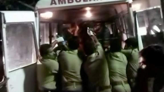 Officials put an injured person into an ambulance.