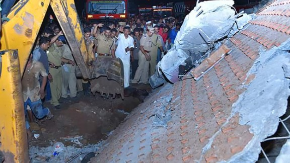 Indian officials and bystanders gather beside a collapsed building after the fire.