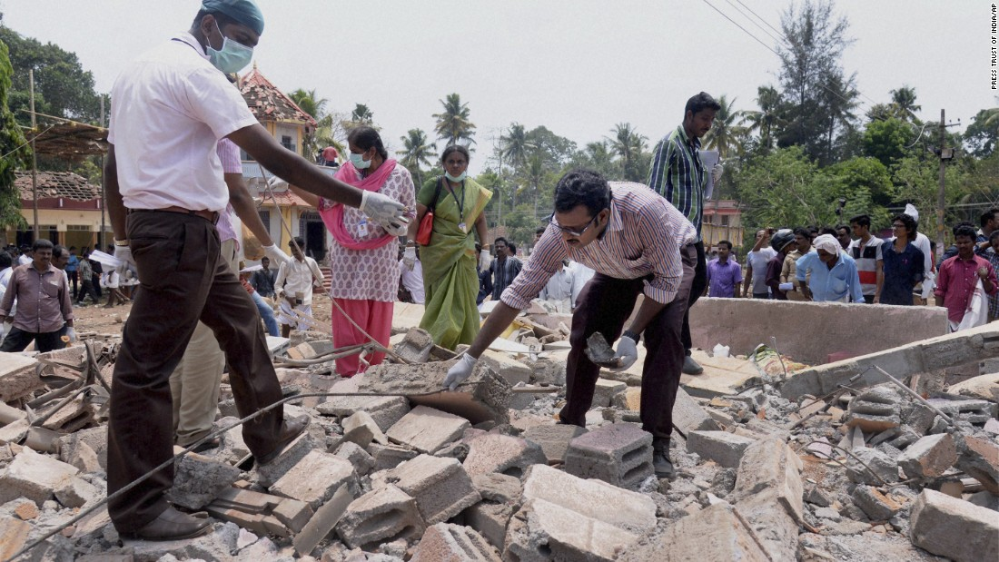 People search through the debris of a a collapsed building after a massive fire broke out during a fireworks display at the Puttingal temple complex in southern India on Sunday, April 10.  Scores of people were killed and hundreds more injured in the fire, caused when an unauthorized fireworks show ignited a separate batch of fireworks that were being stored at the temple complex.