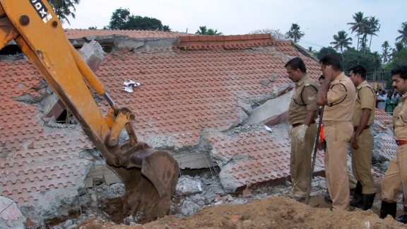Indian officials look on as an excavator moves debris from a collapsed building after an explosion and fire at The Puttingal Devi Temple in Paravur early April 10, 2016.A massive fire swept through a temple in southern India, killing more than 100 people after thousands gathered to watch an illegal fireworks display. More than 280 others were injured in the fire that engulfed the Hindu temple complex in Kerala state, where crowds had built up during the night for a festival that boasted the fireworks show. / AFP / STR        (Photo credit should read STR/AFP/Getty Images)