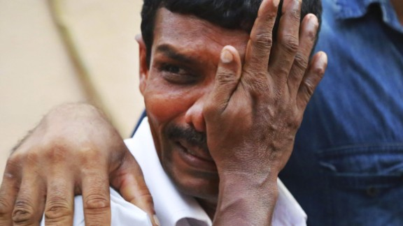 An unidentified man weeps as bodies of victims lie outside a morgue at the Kollam district hospital.