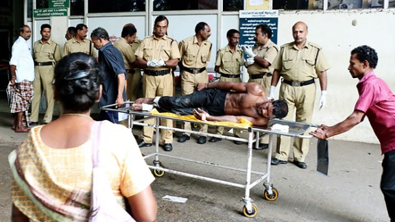 Indian medical officials transport an injured man from a vehicle into a hospital in Paravur, India.