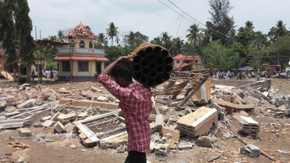 A man carries empty shells of fireworks past a collapsed building  at the Puttingal temple complex.