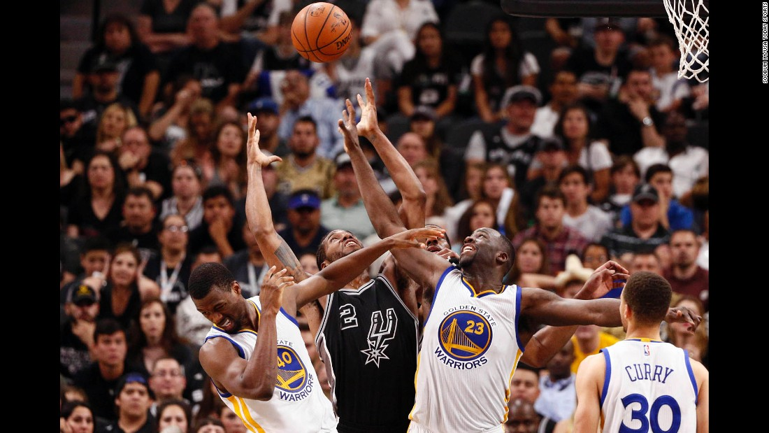 San Antonio's Kawhi Leonard, center, battles for a rebound with Golden State's Harrison Barnes, left, and Draymond Green during an NBA game in San Antonio on Sunday, April 10. Golden State won the game 92-86, tying the all-time NBA record for wins in a season.