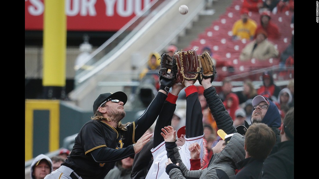 "Pittsburgh first baseman John Jaso, left, reaches for a foul ball during a game in Cincinnati on Saturday, April 9. He was unable to make the diving catch, but he <a href=""http://m.mlb.com/cutfour/2016/04/09/171379814"" target=""_blank"">helped up a fan</a> he knocked over on the attempt."