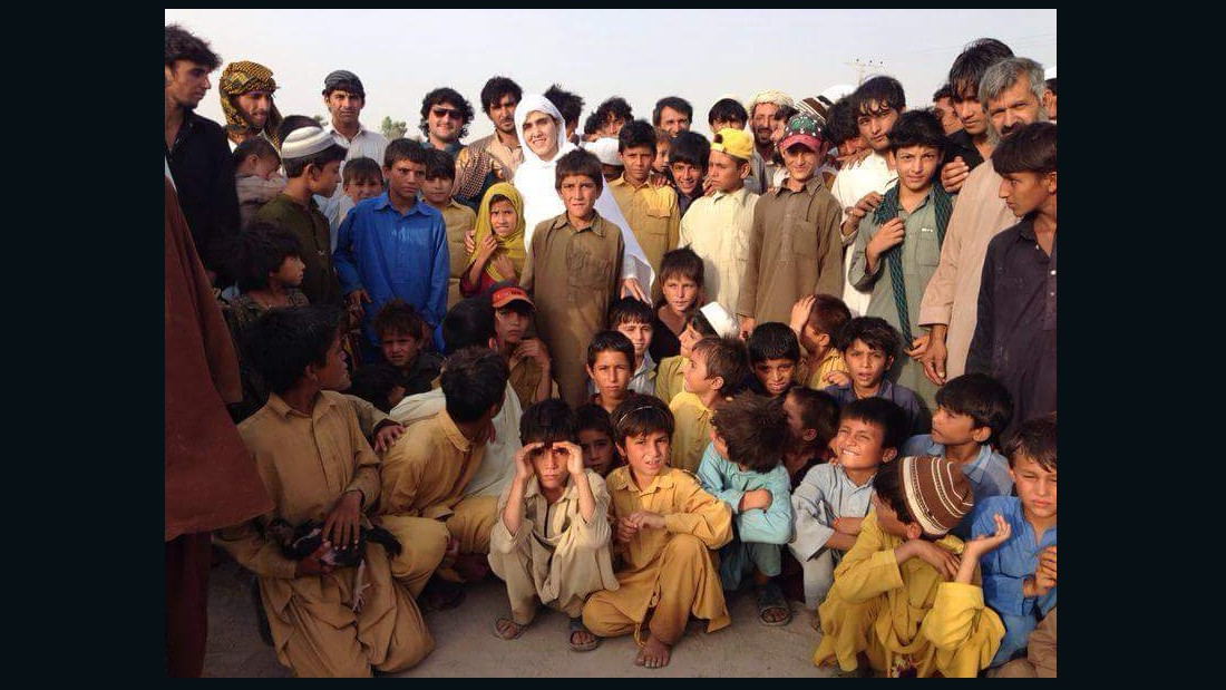 Maria Toorpakai standing among Pashtun children evacuated from their tribal land due to tensions between the army and extremist factions. She organized a special squash event in Islamabad that brought all the displaced children over in hired buses.