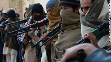 Former Taliban fighters hold weapons they plan to return in a 2015 reconciliation event in Jalalabad, Afghanistan.