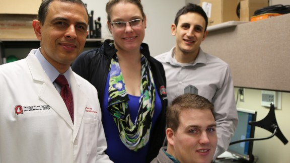 Patient Ian Burkhart, seated, poses with members of his research team during a neural bypass training session.