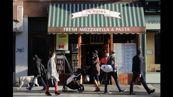 People stroll past an Italian food shop in the Park Slope neighborhood in Brooklyn, where  New York Mayor Bill de Blasio lived before his election.