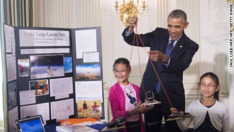 US President Barack Obama holds a homemade spacecraft that was attached to a weather balloon and launched 78,000 feet up into the atmosphere by 11-year-old Rebecca Yeung (L) and 9-year-old Kimberly Yeung (R) as he tours the 2016 White House Science Fair in the East Room at the White House in Washington, DC, April 13, 2016. / AFP PHOTO / SAUL LOEBSAUL LOEB/AFP/Getty Images