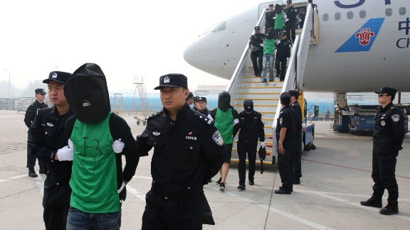 In this photo released by Xinhua News Agency, Chinese suspects involved in wire fraud are escorted off a plane upon arriving at the Beijing Capital International Airport in Beijing on Wednesday, April 13, 2016. The deportation of nearly four dozen Taiwanese that
