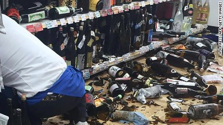 A shop clerk cleans broken wine bottles following an 6.4-magnitude earthquake in Kumamoto Japan on April 14.