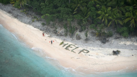 """A man waves life jackets next to a """"help"""" sign made up of palm fronds in this photo released by the U.S. Navy on Sunday, April 10. The Navy and Coast Guard <a href=""""http://www.cnn.com/2016/04/08/politics/castaways-rescue-help-sign/"""" target=""""_blank"""">rescued three castaways</a> who had been stranded on Fanadik Island for three days. The remote Pacific island, part of the Federated States of Micronesia, is about 2,600 miles southwest of Honolulu."""