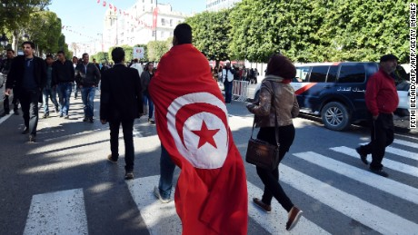 TOPSHOT - A Tunisian man wears a cloth with a print of his national flag during a rally on January 14, 2016 in the Habib Bourguiba Avenue in the capital Tunis to mark the fifth anniversary of the 2011 revolution. Thousands gathered in the Tunisian capital to mark the fifth anniversary of the overthrow of longtime dictator Zine El Abidine Ben Ali in the uprising that inspired the Arab Spring.   / AFP / FETHI BELAID        (Photo credit should read FETHI BELAID/AFP/Getty Images)