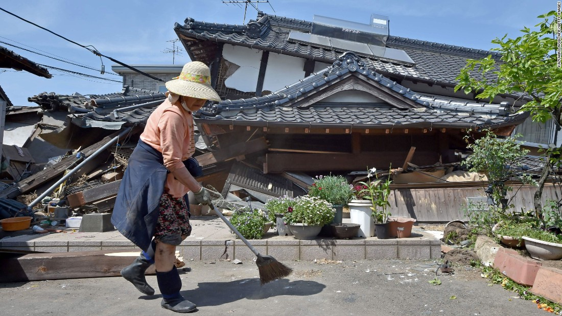 A woman cleans up in front of her collapsed house in Mashiki on April 15.