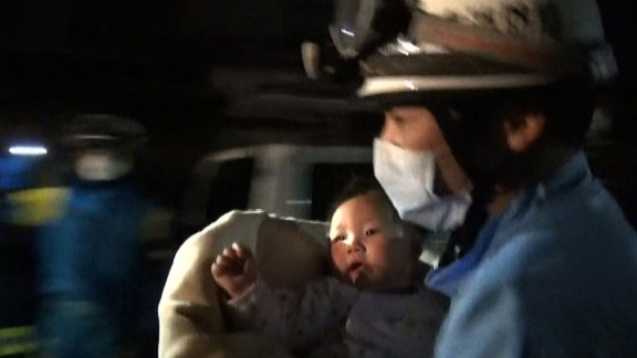 A rescue worker carries an 8-month-old girl after she was pulled from rubble in Mashiki on April 15.