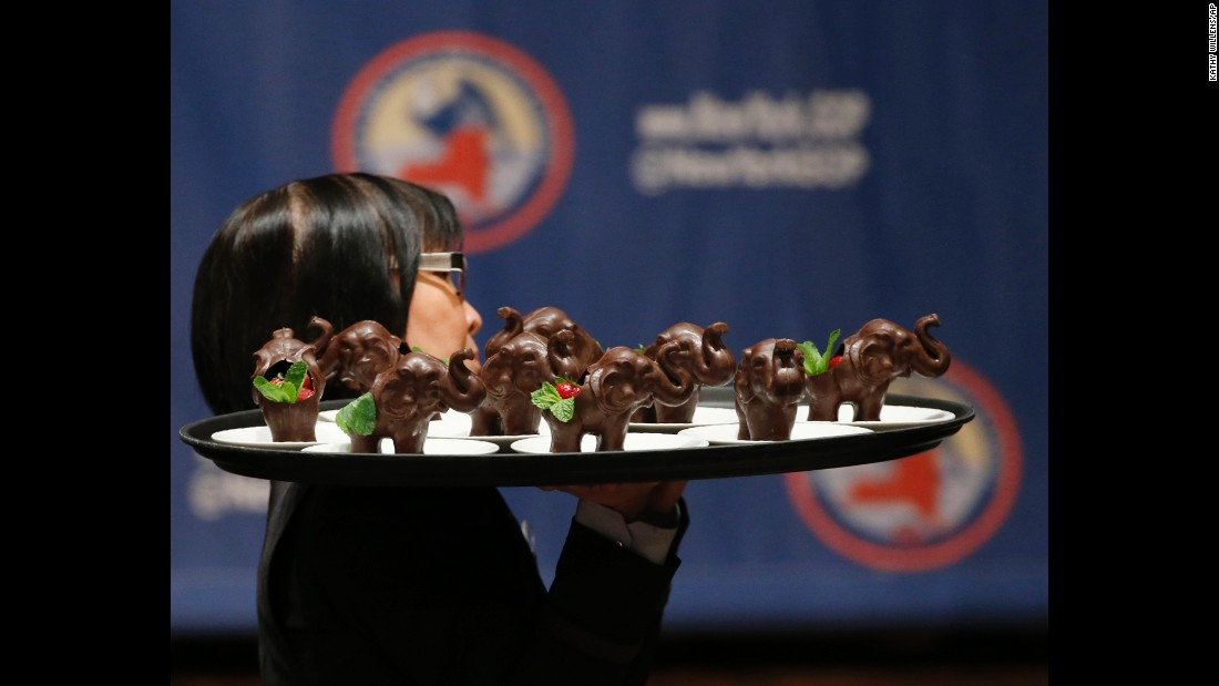 A woman carries a tray full of chocolate elephants before a Republican Party gala in New York on Thursday, April 14.