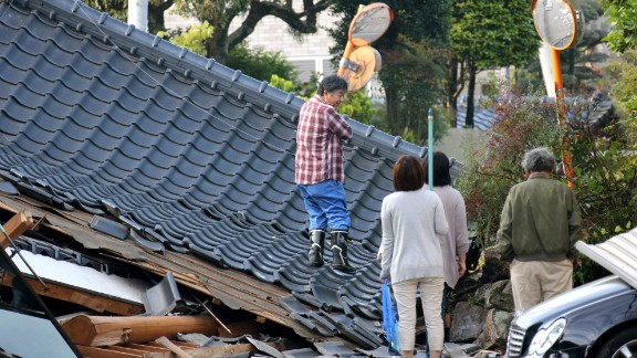 Residents look for an access to their homes on a road blocked by a collapsed house in Mashiki on April 16.
