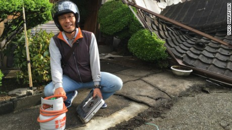Yoshitada Shimamura holding a gas canister recovered from his destroyed home.