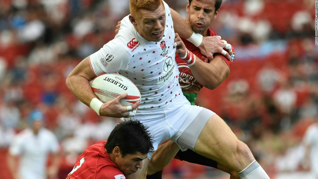 England's James Rodwell (C) struggles through Portugal players during their match at the Singapore Rugby Sevens tournament on April 16, 2016.