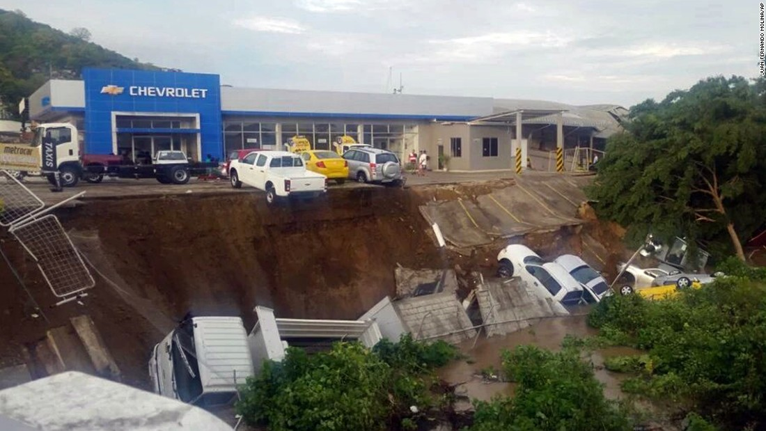 Vehicles from a car dealership hang on a precipice caused by an earthquake induced landslide in Portoviejo, Ecuador, on April 17.