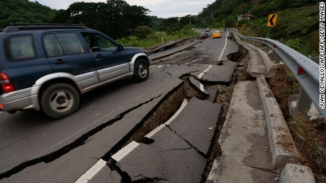 A vehicle rolls on a cracked route after a 7.8-magnitude quake in Chone, Ecuador on April 17, 2016.  At least 246 people were killed when a powerful earthquake struck Ecuador, destroying buildings and a bridge and sending terrified residents scrambling from their homes, authorities said Sunday. / AFP / JUAN CEVALLOS        (Photo credit should read JUAN CEVALLOS/AFP/Getty Images)