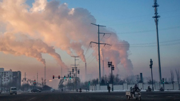 Chinese workers commute as smoke billows from a coal fired power plant on November 25, 2015 in Shanxi, China.