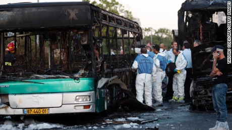 Israeli forensics search at the scene of an explosion on a bus in Jerusalem on April 18, 2016.