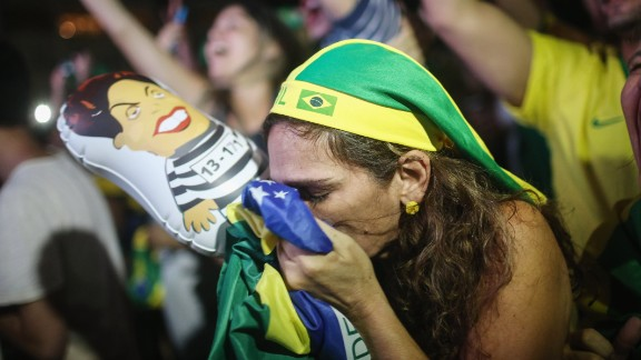 A pro-impeachment supporter kisses a Brazilian flag while watching a live television broadcast moments after lower house deputies vote to approve the motion to continue the impeachment process.