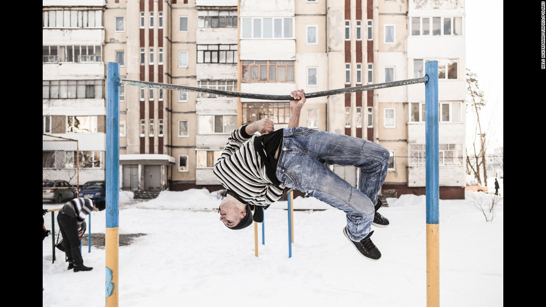 A young man performs acrobatics on a fixed bar at a playground in Slavutych. There aren't many career options in the area and there's not much to keep young people entertained, Ackermann said.
