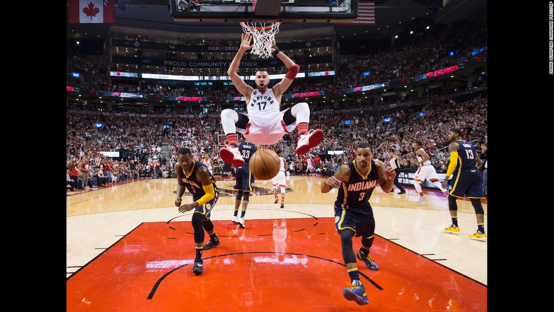 Toronto Raptors' Jonas Valanciunas, center, dunks the ball past Indiana Pacers' Lavoy Allen, left, and teammate George Hill during the second half in Game 1 in the first round of the  NBA basketball playoffs in Toronto on Saturday, April 16.