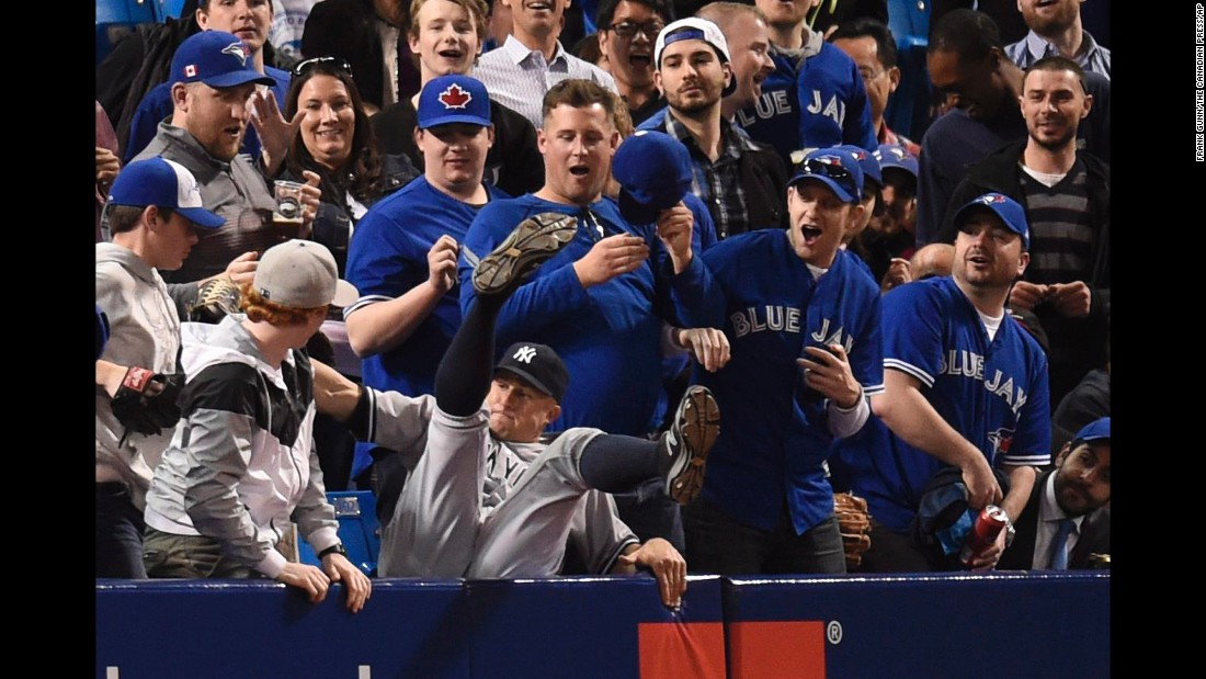 New York Yankees' Brett Gardner falls into the stands after catching a foul ball hit by Toronto Blue Jays' Ryan Goins during the third inning on Thursday, April 14, in Toronto.