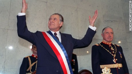 FILE - New Chilean President Patricio Aylwin (L) gestures on March 11, 1990 in Valparaiso, Chile, after receiving the presidential sash during inaugural ceremonies, as outgoing President Augusto Pinochet (R) looks on.  Patricio Aylwin, the first president of Chile after its return to democratic rule following Pinochet's dictatorship, died on April 19, 2016 at the age of 97. / AFP / STR        (Photo credit should read STR/AFP/Getty Images)