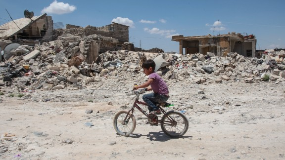 TAL ABYAD, SYRIA - JUNE 20: (TURKEY OUT) A boy rides his cycles in the streets of the destroyed Syrian town of Kobane, also known as Ain al-Arab, Syria. June 20, 2015. Kurdish fighters with the YPG took full control of Kobane and strategic city of Tal Abyad, dealing a major blow to the Islamic State group