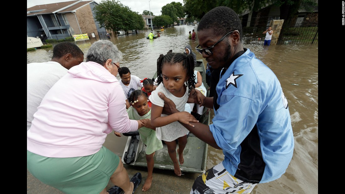 A child is lifted from a boat after being rescued from her flooded apartment in Houston on Monday, April 18.