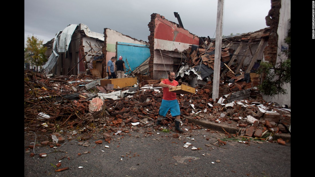 Residents salvage furniture from the remains of their house, which was hit by a tornado in Dolores, Uruguay, on Saturday, April 16.