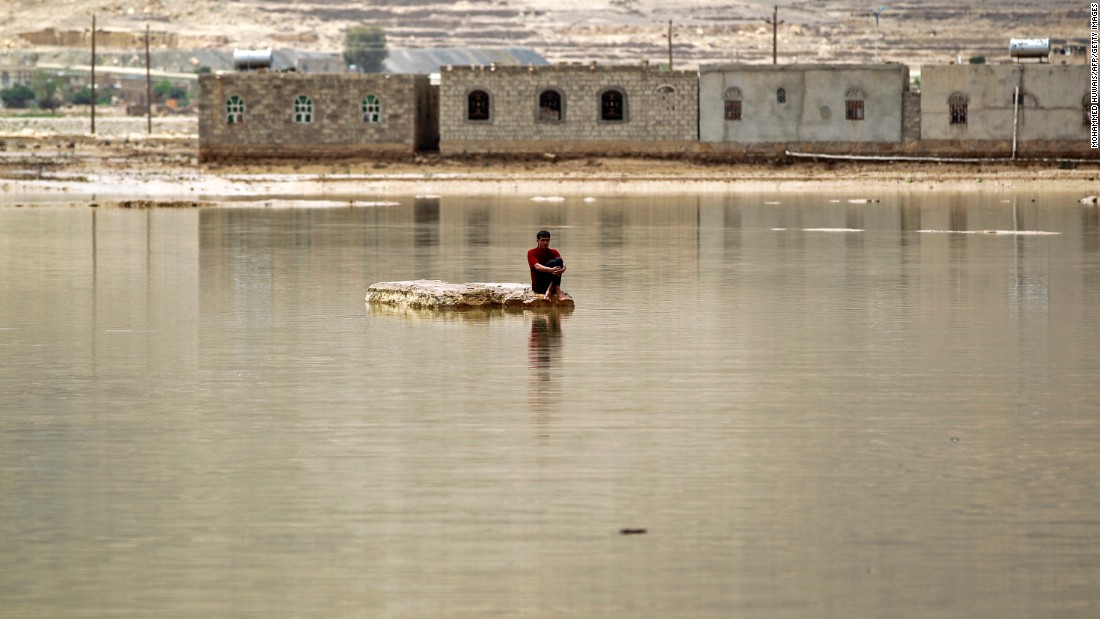 A man sits on a rock in Amran, Yemen, after heavy rain flooded a street on Friday, April 15.