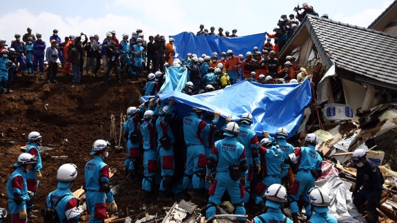 Rescuers prepare to remove the body of a woman found in a house destroyed by a mudslide in Minamiaso on Tuesday, April 19, in the aftermath of a 7.0-magnitude quake on Kyushu Island. The same region was hit by a 6.2-magnitude quake on Thursday, April 14.