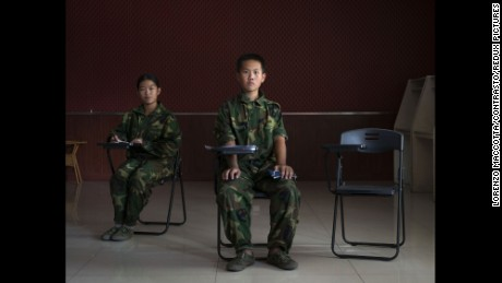 "China, Jinan, Shandong province, October 2015 -  Portrait of Xu Antai (center), 11 years old, and Jiang Yu (left), 14 years old, in a class of the ""Ya Bo center"", a military boot-camp for reeducation of young people who are by the majority suffering from excessive online game playing. Xu Antai has been living in the boot-camp for 4 months, and Jiang Yu for 6 months.  