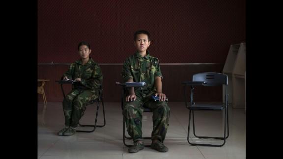 """China, Jinan, Shandong province, October 2015 -  Portrait of Xu Antai (center), 11 years old, and Jiang Yu (left), 14 years old, in a class of the """"Ya Bo center"""", a military boot-camp for reeducation of young people who are by the majority suffering from excessive online game playing. Xu Antai has been living in the boot-camp for 4 months, and Jiang Yu for 6 months.  >< Cina, Jinan, provincia dello Shandong, ottobre 2015 - Ritratto di Xu Antai, un bambino di 11 anni (centro), e di Jiang Yu (sinistra), una ragazza di 14 anni, in una classe presso il """"centro Ya Bo"""", un boot-camp militare per la rieducazione di giovani problematici di cui la maggior parte soffre di un uso eccessivo di videogiochi online. Xu Antai vive nel centro da 4 mesi mentre Jiang Yu vive nel centro da 6 mesi."""
