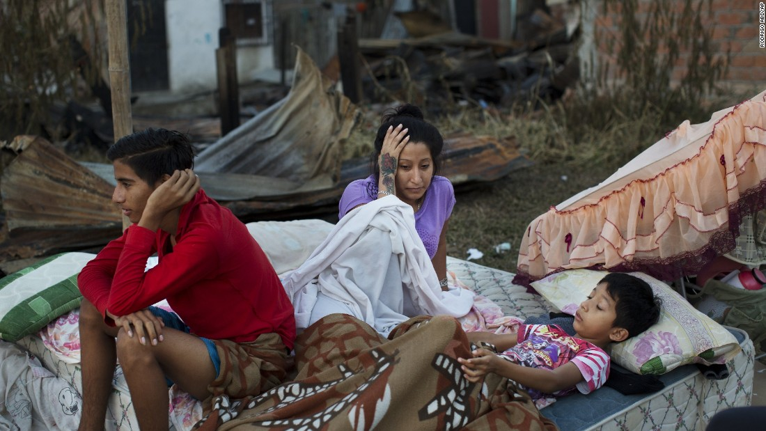 A Manta family wakes up April 19 after sleeping outside their home destroyed in the quake.