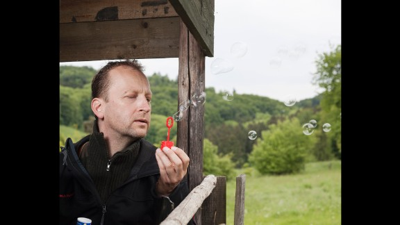 Jens Stormer, a hunter, blows soap bubbles to see which way the wind is going. This way, animals can